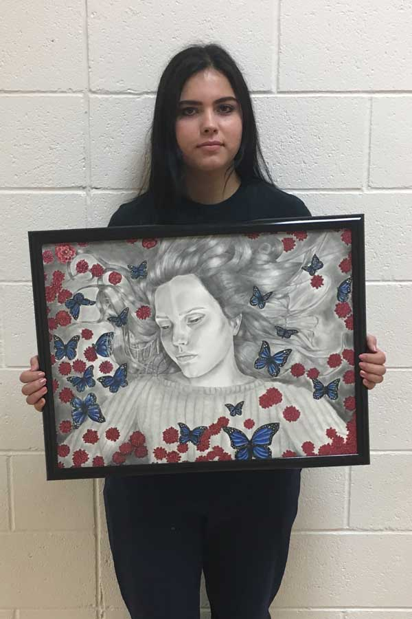 Isabell+Martinez+holding+her+self+portrait.+