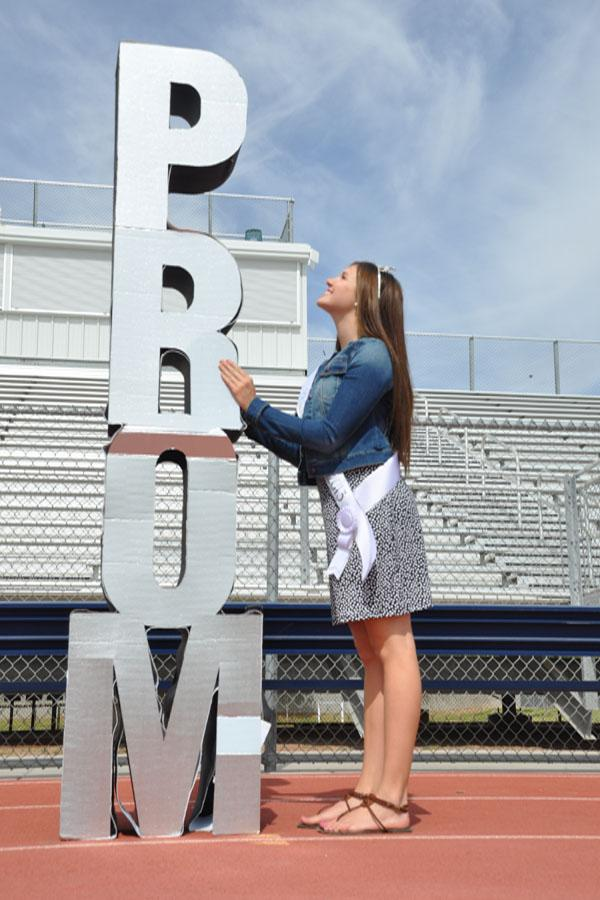 Senior Taylor Williams poses next to a prom sign