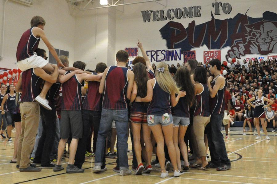 Varsity track runners celebrate together in front of fellow students.