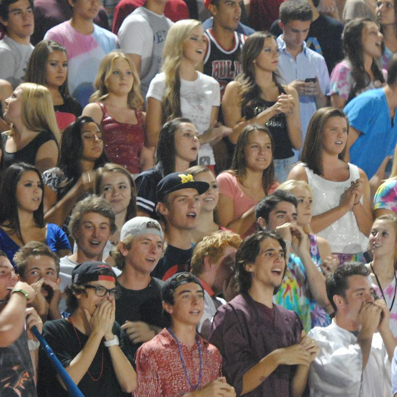 Students celebrate together during a Friday night home football game.