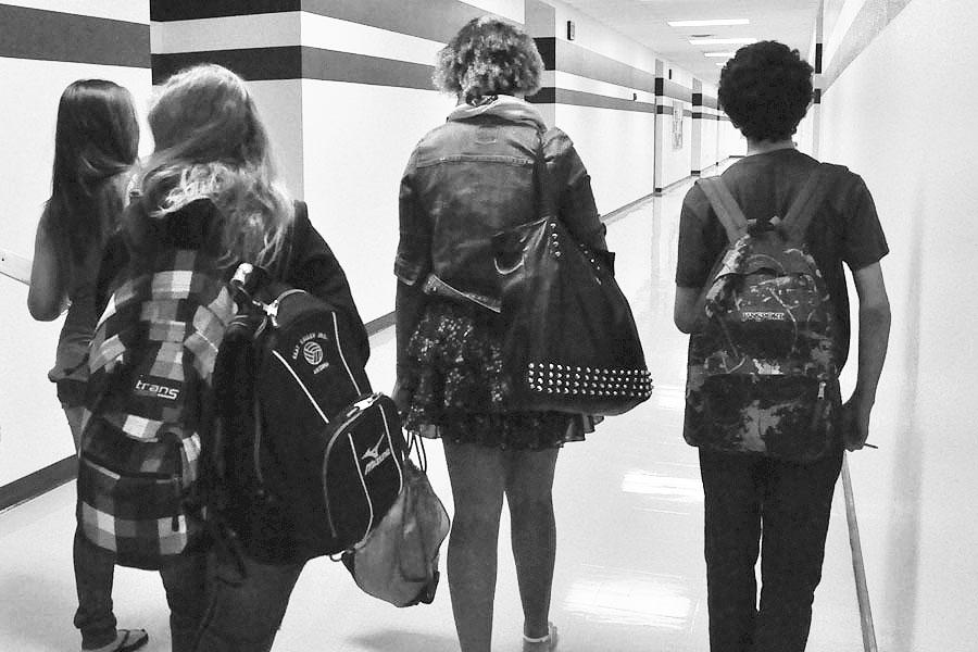 Students walking down PHS hallways carrying their bags. Since PHS has no lockers for students, they are forced to keep everything on them at all times.