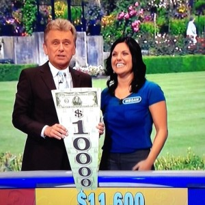 "Longtime ""Wheel of Fortune"" host Pat Sajak shows off Megan Freemole's $1000 prize. Freemole, a Spanish teacher and track coach, finished in second place during ""Wheel's"" teacher week in October."