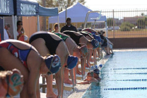 Multiple girl swimmers line up in preperation for a swim meet.