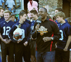 Bruce Cooper of Channel 12 News, broadcasts PHS football players handing out turkeys at Basha's Supermarket.