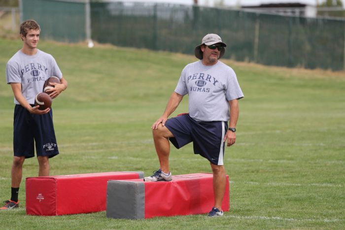 Coach Todd Rogers (right) and senior Jackson Spilsbury work together during PHS summer football camp in Flagstaff, Arizona.