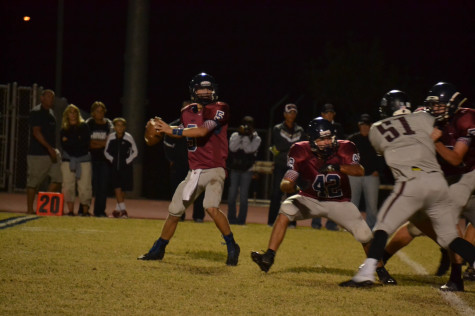 Quarterback Alec Monte drops back to pass and looks for an open receiver.