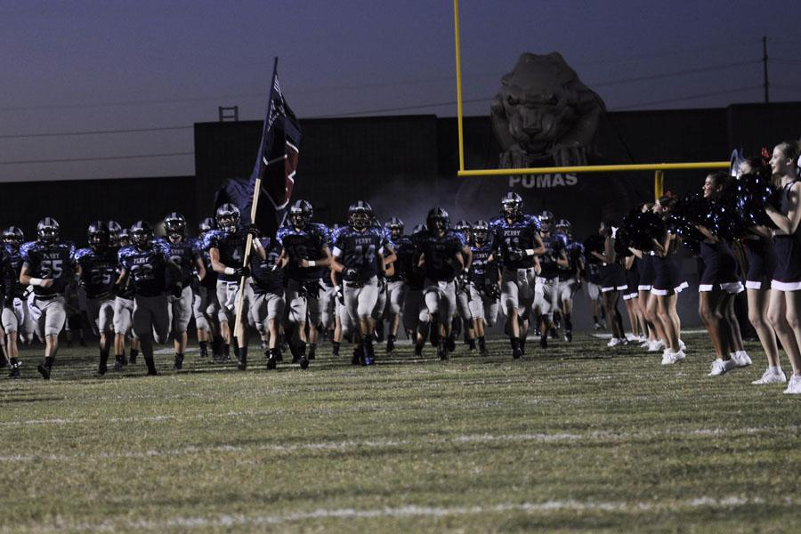 The football team takes the field before their homecoming game against Gila Ridge in September. Football players, like many PHS athletes, have a wide variety of pre-game superstitions and rituals.