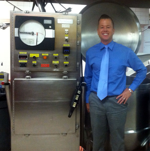 Wesley Delbridge standing next to  the Cook/Chill Kettle and Temberature Monitoring System at Central Kitchen