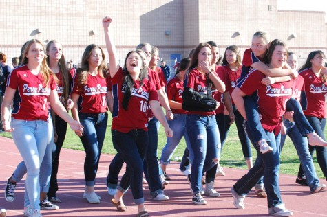 The student body cheer as Perry Varsity softball walks across the track at the spring assembly.