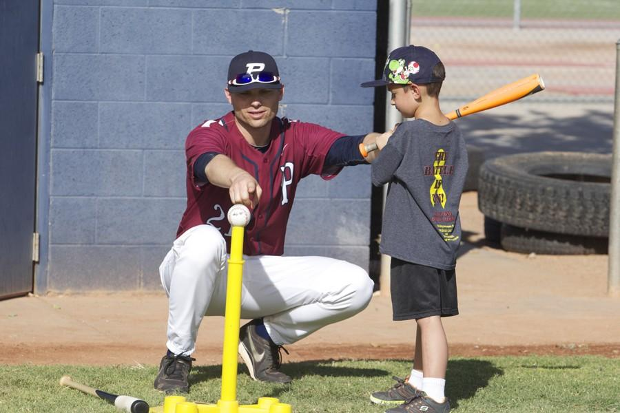 Coach Damien Tippett teaches Trajen Curtis (7) how to hit a baseball at the Catchers' Crushing Cancer Clinic on Sept. 19. Curtis, a CUSD second grader, is a cancer survivor.