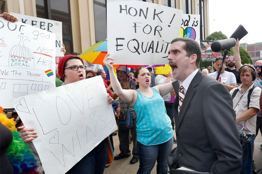 Street preacher Jeffrey Shook, with Unity Baptist Church in Hickory N.C., preaches to Kim Davis protestors in front of the Carl D. Perkins Federal Building in Ashland, Ky., on Thursday, Sept. 3, 2015. Davis was found guilty by U.S. District Judge David Bunning of contempt of court for refusing to issue marriage licenses in Rowan County, Ky.