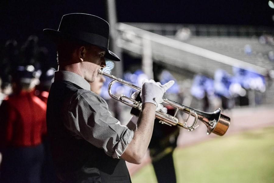 Senior Connor Maxwell practices his trumpet solo before taking the field for a halftime performance.