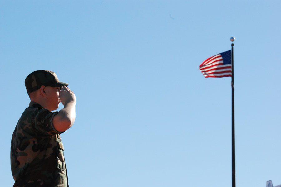 Senior Jon Allen salutes the American flag just inside John Wrenn Stadium. Students in the ROTC program learn vital lessons for future careers in the military.