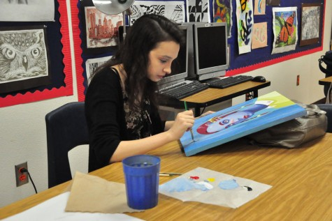 Abigail Starkey working on a painting in her art class.