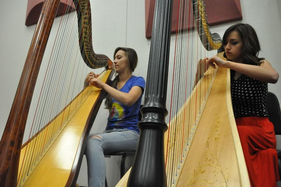 Senior Victoria Bull (left) and junior Hannah Butcher practice harp during their first hour chamber orchestra class. Bull and Butcher began playing harp when they both were nine, and joined orchestra when they were freshmen.