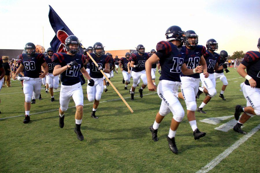 Perry's Varsity football team heads on to the field for their first game of the season.