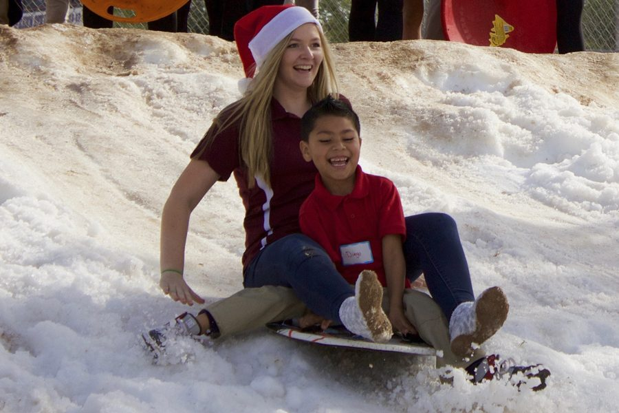 A+Stugo+volunteer+and+a+child+from+the+smiles+for+the+season+event+sled+down+the+fake+snow+station+they+had+set+up+on+Wednesday%2C+December+7th.+Shot+by+Cole+Simpson.