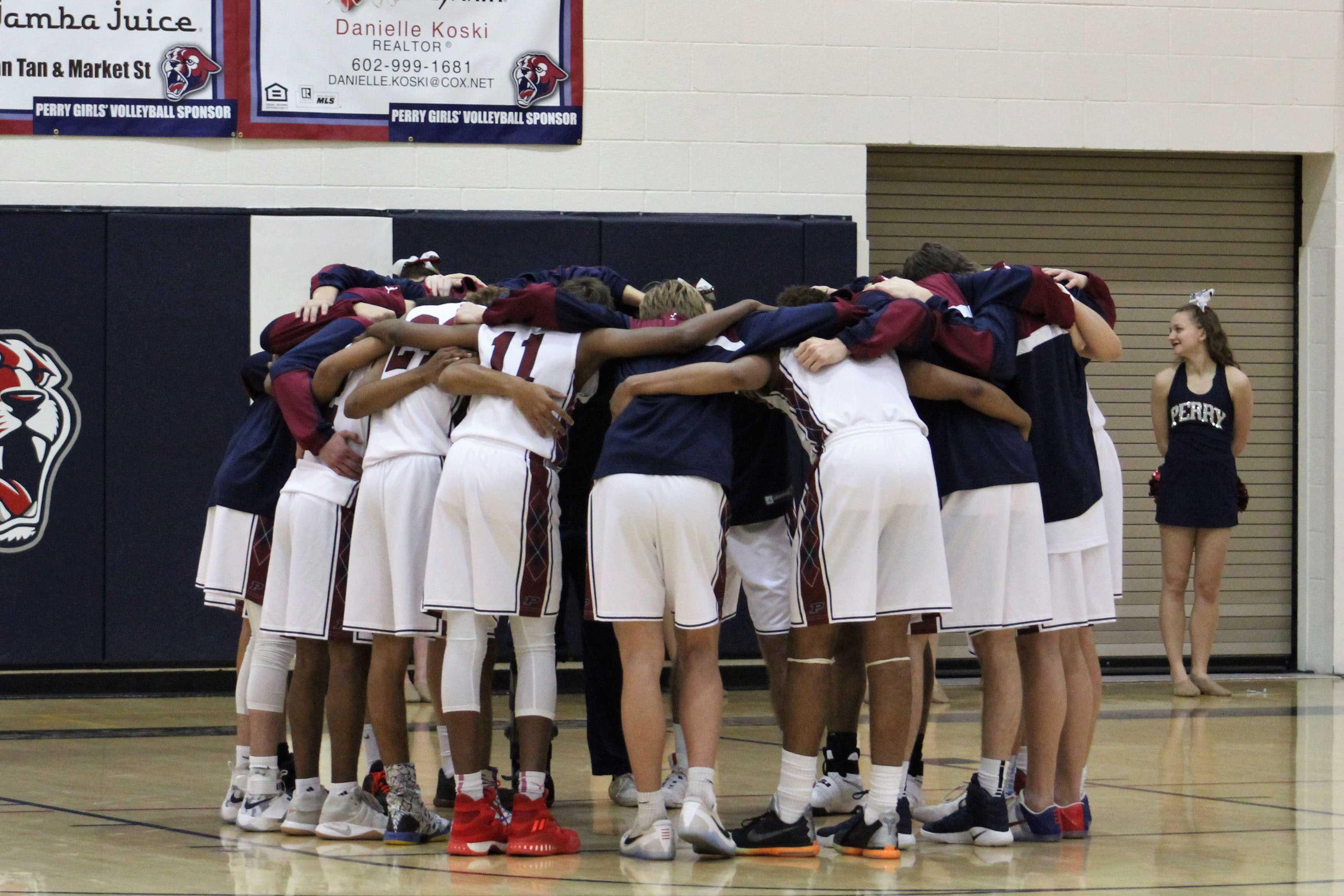 Boys basketball team huddles during game.