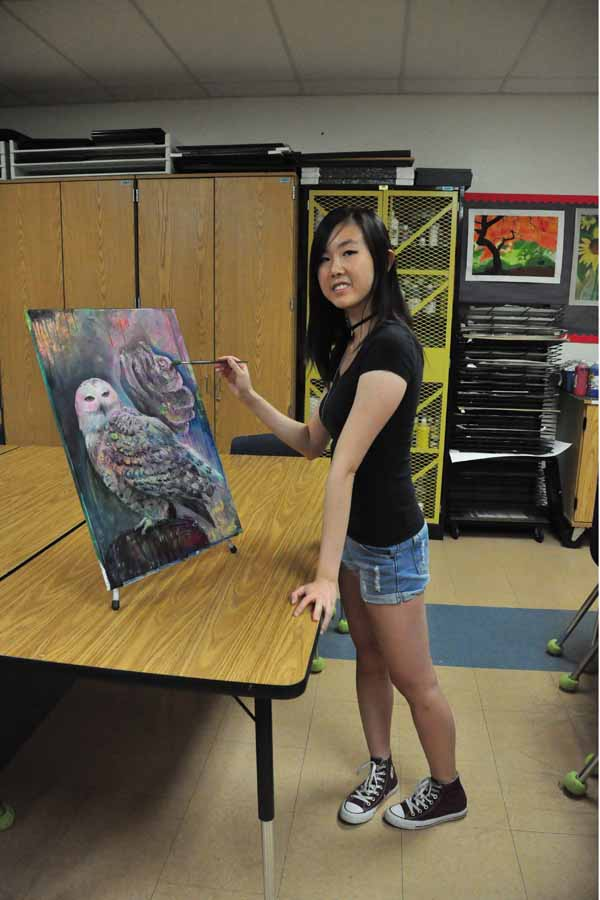 Senior Selina Lo posing with her owl spray paint project.