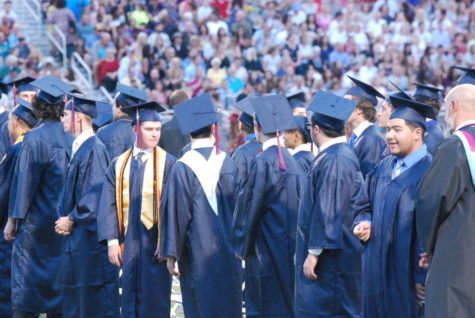 Male graduates preparing to walk. Parents and family filled the bleachers fom top to bottom.
