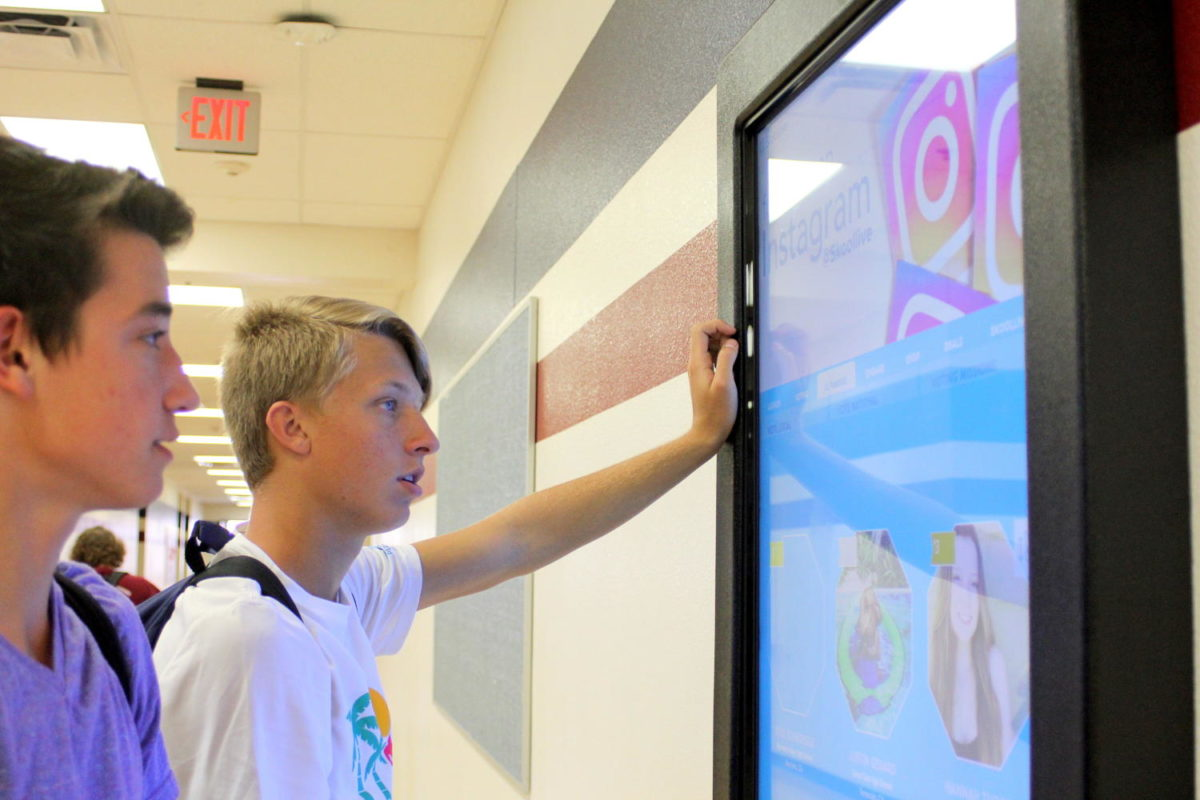 Juniors Marshall Conley and Thomas Smith examine the kiosk. SkoolLive was implemented into the PHS campus this year.