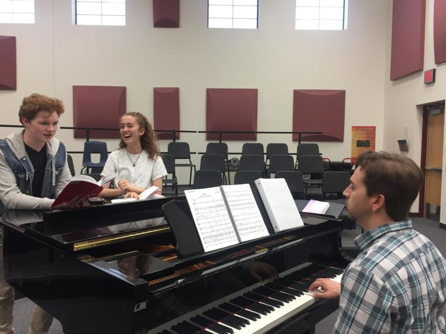 Two+students+who+are+playing+a+main+role+in+the+upcoming+winter+musical+practice+there+music.+