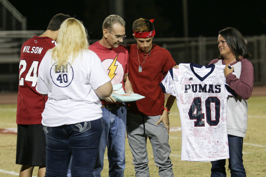 On+Nov.+3%2C+the+football+Touchdown+Club+presented+the+Mason+Family+with+Brayden+Mason%27s+jersey.+From+left%3A+sophomore+Cody+Horcasitas%2C+mother+Karen+%28not+pictured%29%2C+father+Frank%2C+and+sophomore+AJ+Owens+accept+the+gift%2C+which+was+signed+by+Brayden%27s+teammates+and+friends.
