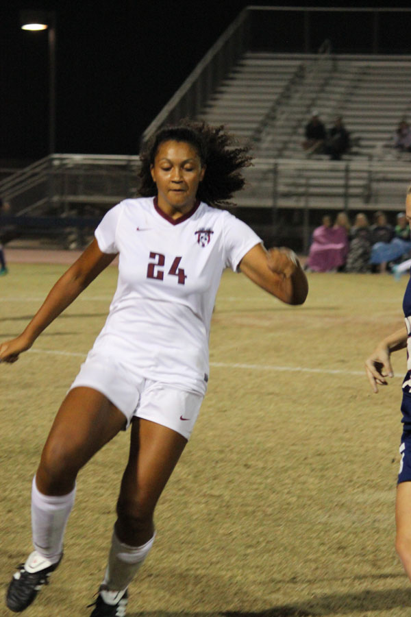 Jackie Gilbert (24)  is running to get the ball from the Pioneers player.