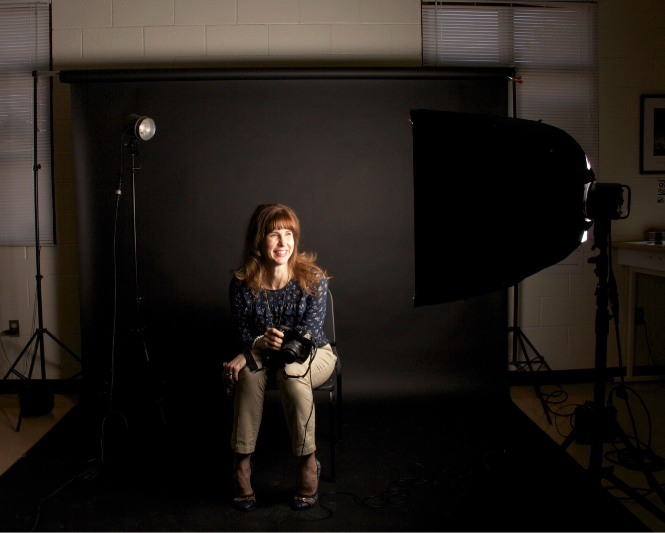 Elizabeth Tompkins sits in the class room studio as a student takes her portrait.