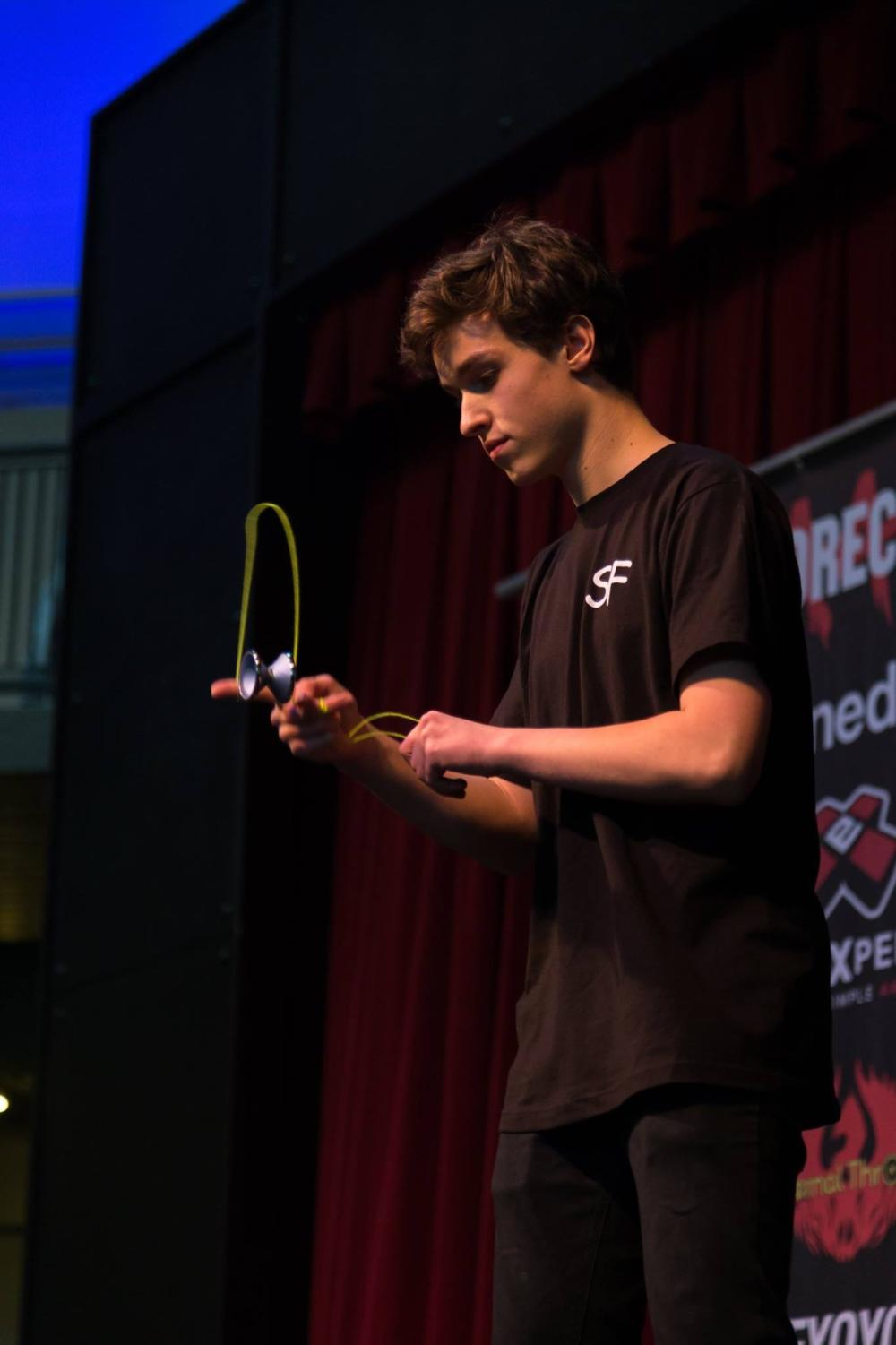 Collin Ellingson performing tricks at a yo-yo competition, participating under his team of SF.