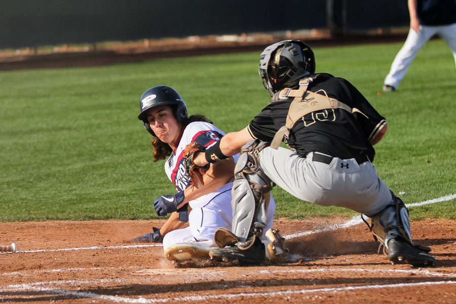 Senior Michael Zinter slides in under the tag against Queen Creek.