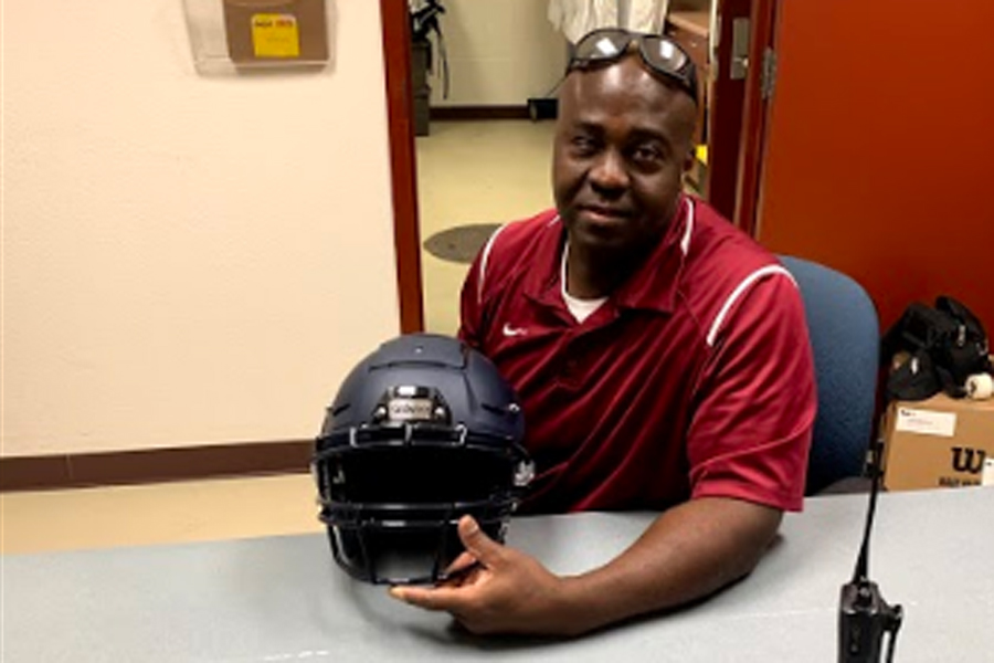 Athletic Equipment Manager Derwin (DC) Coleman is holding up Schutt F7