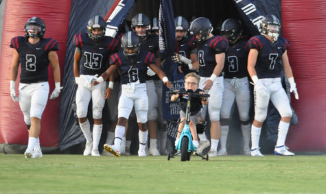 Freshman Trey Lane leads the Varsity football team out for their first home game.