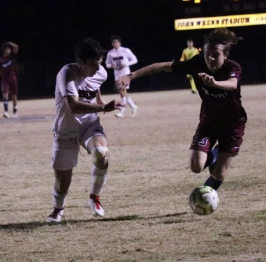 Sophomore defender Kade Mckinzie dribbling up field against opposing team Red Mountain.