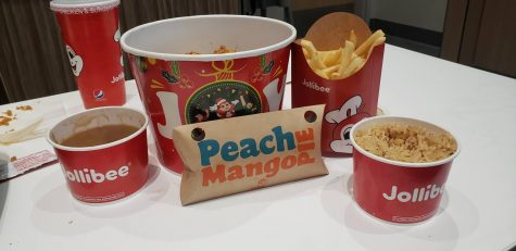 Jollibee's 6-piece Chickenjoy bucket with gravy, fries, adobo rice, and peach mango pie.