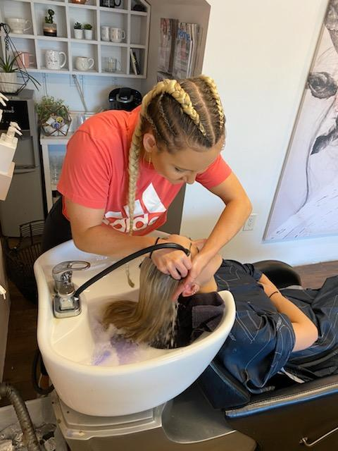 Viola Rosa hairstylist Hailey Hull washes a client's hair, unable to adhere to the six-foot rule Gov. Ducey says all essential services will follow.