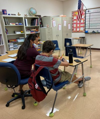 Special Education teacher Caroline Cook helping freshman Cole Kostoryz with his assignment.