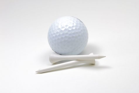 Golf ball accompanied with two white tees.