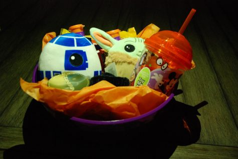 A fully assembled Halloween boo basket. Full of cookies, a Halloween themed cup, and other treats.