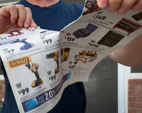 An irritated customer rips up Black Friday spam mail. Many shoppers will be staying home this year because of COVID-19.