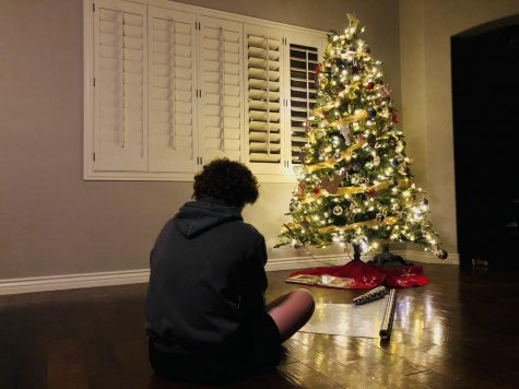 Sophomore Kacin Allred wraps presents near the Christmas tree waiting for the big day to come. Christmas, which is less than two weeks away, has changed significantly this year due to COVID-19.