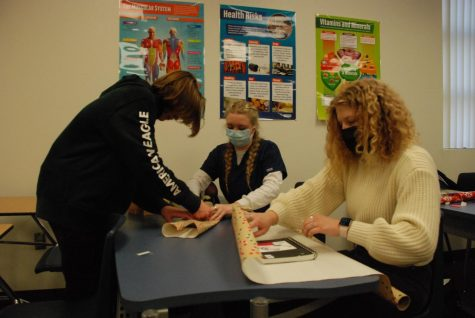 Freshman Samuel Spencer, Senior Aubrey Clouse, and Junior Maddy Jex work together to wrap gifts. These festive presents will be gifted to low-income students.