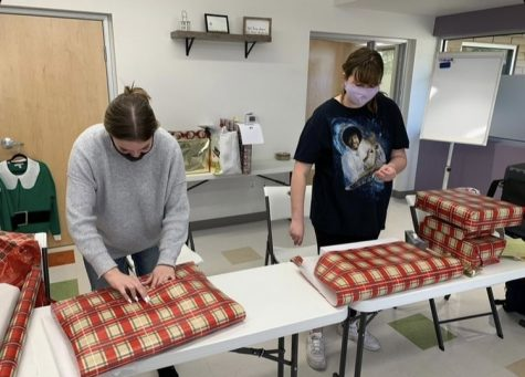 Kendall Ramsey and Kyla Christensen wrap presents at a LEO Club sponsored service event.