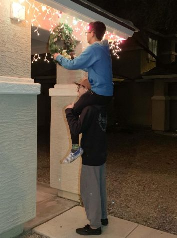 Seniors Bryce Harger and Ethan Le are hanging up a Christmas wreath. Le is on Hargers shoulders while hanging the wreath underneath a house entrance.
