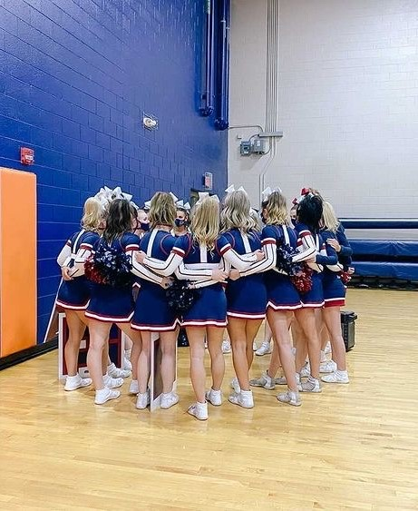Varsity cheer huddles together before taking the mat at last weeks competition. The team placed 2nd out of 17 teams and qualified to compete at state in March.