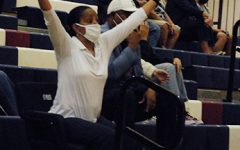 Supportive parent, Rachell Tucker, cheers on the boys' varsity basketball at home against Red Mountain.