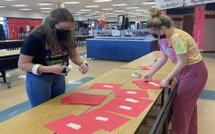 Ella Hanks and Bridget Pitts from StuGo working on putting up the Valentines Day hearts with all the teachers and students names on them.