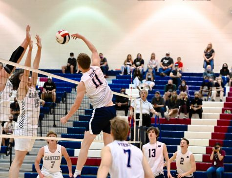 Number 11, senior Camden Neimann, nails a shot over the net while Casteel tries desperately to defend. Neimann is the current team captain for the varsity team.