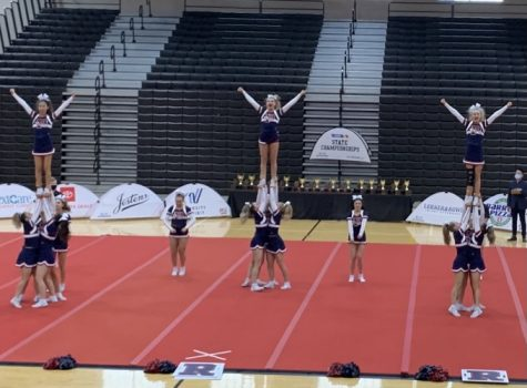 Varsity show cheer takes the mat at state in March. Both pom and cheer will compete at nationals in Florida April 21-25