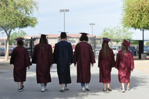 Seniors: Gavin Brennan, Makayla Premo, Anna Myers, Dayton Jones, Ashlyn Minor, and Nadine Loureiro wear their cap and gown while walking off-campus. After their abnormal four years of high school these seniors are ready to start their new life.